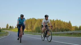 Two professional road cyclists ride their bikes on a hill. Hand held shot of two strong cyclists female and male on. Their training on a warm but windy summer stock video