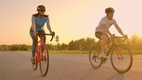 Two professional road cyclists ride their bikes on a hill. Hand held shot of two strong cyclists female and male on. Their training on a warm but windy summer stock video footage