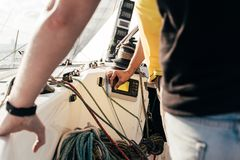 Sailors on sailboat or yacht observe devices. Two professional sailors, captain and helper, control boat with steering wheel and rudder, analize and observe data Royalty Free Stock Image