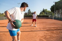 Tennis players warming up. Two professional tennis players warming ub by throwing a medicine ball to each other Royalty Free Stock Photography