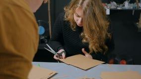Two professional women decorators, designers working with kraft paper. Two professional women decorators, designers cutting kraft paper and making envelopes at stock footage