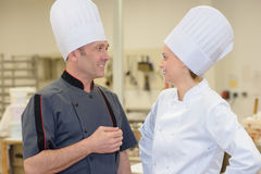 Two professionals chefs talking and smiling in kitchen Royalty Free Stock Photos