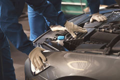 Two professionals examining cars engine royalty free stock images