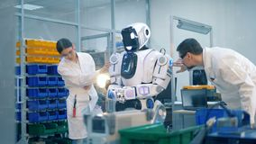 Two professionals are inspecting a robotic humanoid. 4K stock video