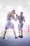 Two professionl boxers are fighting on arena Royalty Free Stock Photo