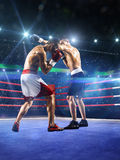 Two professionl boxers are fighting on arena Stock Photography