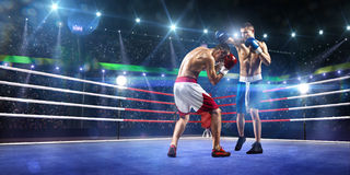 Two professionl boxers are fighting on arena Stock Image