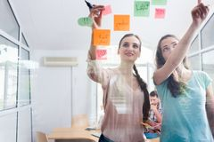 Two proficient female co-workers posting sticky notes in the int Stock Photos