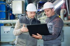 Two protective line worker in factory stock image