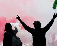 Two protesters after a soccer match with the smoke. On the street Stock Photos