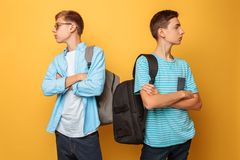 Two proud teenage boys, offended at each other and unwilling to admit their guilt, are isolated against a yellow background royalty free stock photo