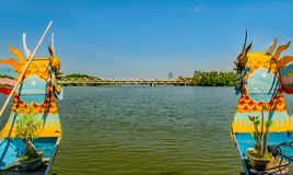 The two prows of a dragonboat approaching a bridge on the Perfume River Hue,Vietnam. The two brightly painter prows of a dragonboat approaching a bridge on the royalty free stock images