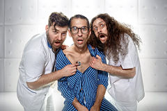 Two psychiatrists examining a funny lunatic. Two odd psychiatrists examining a funny lunatic Royalty Free Stock Photography