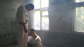 Two psycho men helping and moving on each other in mental hospital. Striking view of two psycho men in white uniforms supporting and helping each other. One of stock video footage