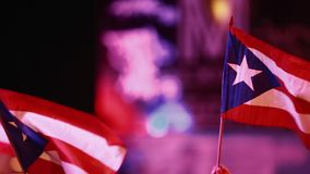 Two Puerto Rican Flags being held at Festival during evening. Evening shot of two Puerto Rican flags being held outdoors at an event.  SInce it is a close-up stock video footage