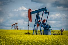 Two pump jacks in a canola field in Saskatchewan, Canada. Two pump jacks in a canola field in bloom in Saskatchewan, Canada stock photos