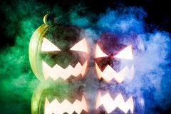 Two pumpkins for Halloween on blue and green smoke. On black background Royalty Free Stock Images