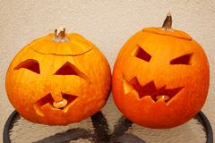 Two pumpkins of Halloween lie on table stock photography