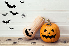 Two pumpkins with painted faces, decorative spiders and bats on Stock Images
