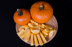 Two pumpkins and slices on wood board in a black backgroung stock image