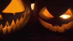Two pumpkins are on the table, and candles are burning around. Halloween art design.  stock video footage