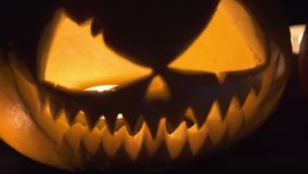 Two pumpkins are on the table, and candles are burning around. Halloween art design.  stock video