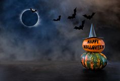 Two pumpkins with witch hat and text HAPPY HALLOWEEN against the stock photos