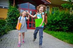 Two pupils of elementary school, boy and girl, on a schoolyard. Royalty Free Stock Image