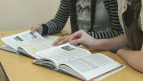 Two pupils flip pages of textbook at lesson. Two pupils sitting at the desk flip the pages of textbook at the lesson stock video
