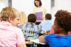 Two Pupils Talking In Class Together Stock Photography