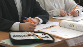 Two pupils write in exercise book with ball pen. Two pupils sit at school desk and write in exercise book with a ball pen stock video footage