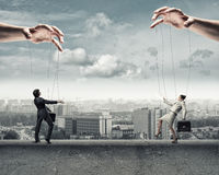 Two puppet businessman. Image of a two puppet businessman standing on against each other, concept of business control Stock Photos