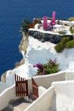 Two purple chairs on balcony of Santorini  island cliff Royalty Free Stock Photos