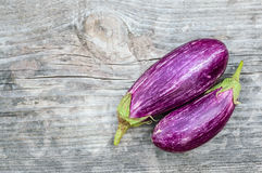 Two purple eggplants on the wooden board Stock Photos