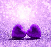 Two purple Hearts on abstract light glitter background Stock Photo