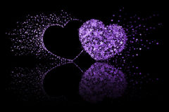 Two purple hearts on black background with reflection effect Stock Photo