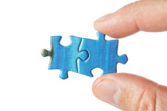 Two puzzle in the fingers. Royalty Free Stock Photography
