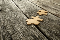 Two puzzle pieces lying on wooden rustic boards. Conceptual of innovation, solution finding and integration Royalty Free Stock Photo