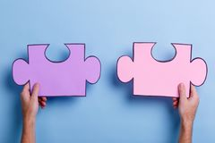 Two puzzles that hold the hands of a man. Close-up. Two large puzzles that hold the hands of a European man. On a blue background. Close-up Stock Photos