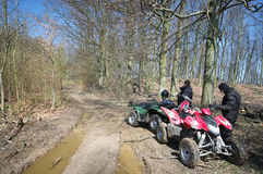 Two quads in forest (ATV). Two quads in a forest standing next to a very muddy track. (ATV Stock Images