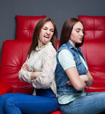 Two quarreling girls sits on red leather couch Stock Photography