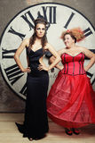 Two Queens posing next to the clock. Stock Photos