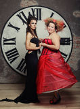 Two Queens posing next to the clock. Royalty Free Stock Photography