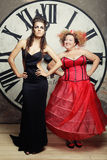Two Queens posing next to the clock. Stock Photography