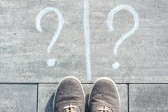 Two question marks  handwritten on an asphalt road with sneakers. Two question marks are handwritten on an asphalt road with sneakers Stock Photo