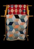 Two Quilts On A Rack. Two vintage quilts displayed on a wooden rack, black iso Royalty Free Stock Images