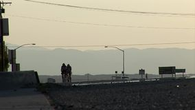 Two RAAM contestants cycle at the sun set stock video footage