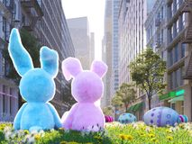 Two rabbits sitting in lawn with easter eggs infront of big city. 3d rendering. 3d rendering. two easter rabbits sitting in lawn with easter eggs Stock Images