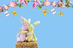 Two rabbits on a straw bale with butterflies and flowers. In front of a blue background Royalty Free Stock Photo