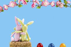 Two rabbits on a straw bale with easter eggs and flowers. In front of a blue background Stock Photo